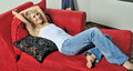 Sexy blonde woman relaxing on red couch Stock Photos