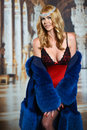 Sexy blonde woman wearing fashionable winter fur coat and seductive red lingerie portrait of very Royalty Free Stock Photography