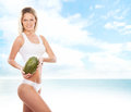 Sexy body of a young and fit woman holding a fresh melon blond in white lingerie the image is taken on light sky background Stock Photo