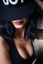 Sexy brunette in cap swag with beautiful breasts with a gold chain and a raspberry red lipstick Royalty Free Stock Image