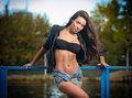 Sexy brunette in denim shorts posing provocatively outdoor portrait of a beautiful sexy woman with denim shorts in a park Stock Photography