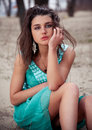 Sexy brunette girl in green dress sitting on sand portrait of Royalty Free Stock Photography