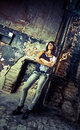Sexy brunette girl leaning against wall at abandoned building Stock Photos