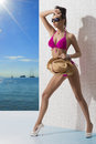 Sexy brunette pink bikini straw hat sunglasses turned three quarters her right arm front Stock Image