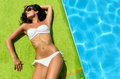 Sexy brunette sunbathing at poolside Royalty Free Stock Photos