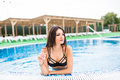 Sexy brunette in the white bikini on the sun-tanned slim and shapely body is relaxing in the swimming pool. Summer vocation Royalty Free Stock Photo