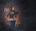 A sexy brunette witch making poison in a pot young and caucasian dark clothes large the image is taken on dark and foggy Royalty Free Stock Image