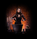 A sexy brunette witch making poison young and caucasian in dark clothes in large pot the image is taken on dark and foggy Royalty Free Stock Photos