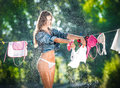 Sexy brunette woman in bikini and shirt putting clothes to dry in sun sensual young female with long legs putting out the washing Royalty Free Stock Photography