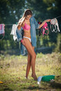 Sexy brunette woman in bikini and shirt putting clothes to dry in sun sensual young female with long legs putting out the washing Stock Images