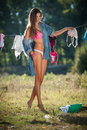 Sexy brunette woman in bikini and shirt putting clothes to dry in sun sensual young female with long legs putting out the washing Royalty Free Stock Photos