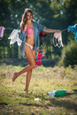 Sexy brunette woman in bikini and shirt putting clothes to dry in sun. Sensual young female with long legs putting out the washing Royalty Free Stock Photo