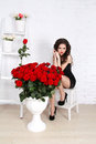 Sexy brunette woman with bouquet of red roses against th wall in modern interior apartment Royalty Free Stock Image