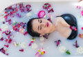 Sexy brunette woman relaxing in hot milk bath with flowers Royalty Free Stock Photo