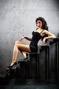 Sexy brunette woman sitting on stairs lying at backyard of building Stock Photos