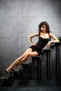 Sexy brunette woman sitting on stairs lying at backyard of building Royalty Free Stock Images