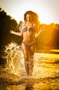 Sexy brunette woman in swimsuit running in river water. Sexy young woman playing with water during sunset. Beautiful woman Royalty Free Stock Photo