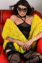 Sexy brunette woman wearing seductive lingerie and luxury fur coat posing on the red couch