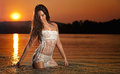 Sexy brunette woman in wet white lingerie posing in river water with sunset on background. Young female at the beach in twilight Royalty Free Stock Photo