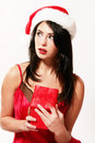 Sexy christmas girl pretty woman with santa hat on and a red negligee holding a small red gift Royalty Free Stock Image