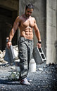 Sexy construction worker shirtless with muscular body showing holding big bricks Stock Photo