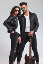 Sexy couple in leather jackets holding electric guitar Royalty Free Stock Photo