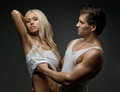Sexy couple muscular handsome guy with pretty woman on dark background Stock Photography