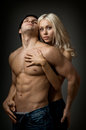Sexy couple muscular handsome guy with pretty woman on dark background glamour light Stock Photography