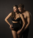 Sexy couple woman and man portrait sensual high waist underwear female in panties kissing boyfriend over black background Stock Photos