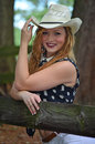 Sexy cowgirl pose wooden fence cowboy hat blonde touching the brim of her and smiling with red lip stick as she poses by a with Royalty Free Stock Image