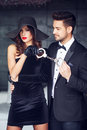 Sexy dominatrix woman holding on handcuffs young macho lover in Royalty Free Stock Photo