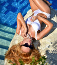 Sexy fashion pretty woman relaxing in blue luxury swimming pool Royalty Free Stock Photo