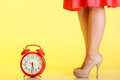 Sexy female legs in high heels and red clock beige standing next to on yellow background time for femininity studio shot Royalty Free Stock Photos
