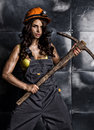 Sexy female miner worker with pickaxe, in coveralls over his naked body Royalty Free Stock Photo