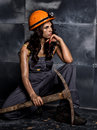 Sexy female miner worker with pickaxe, in coveralls over his naked body, sitting on the floor on backdrop of steel wall Royalty Free Stock Photo