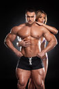 Sexy fit blond girl hugging from behind male bodybuilder standing together over black background Royalty Free Stock Image