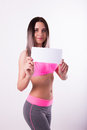 Sexy fitnes brunette in a tracksuit holding empty white board Royalty Free Stock Photo