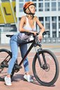 Sexy fitness. Pretty sexy blonde girl with big boobs in white t-shirt posing outdoor on the bicycle Royalty Free Stock Photo