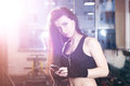 Sexy fitness woman in sportswear resting after dumbbells exercises in gym. Beautiful girl chatting on the phone and relaxing Royalty Free Stock Photo