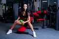 Sexy fitness woman in sportswear resting after dumbbells exercises in gym. Beautiful girl with perfect fitness body drinking from Royalty Free Stock Photo