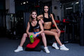 Sexy fitness women in sportswear resting after dumbbells exercises in gym. Beautiful girls with perfect fitness body drinking from Royalty Free Stock Photo