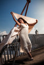 Sexy girl with big white veil in dress standing on bridge Stock Photo