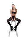 Sexy girl in black pantyhose  and bra sit on chair Royalty Free Stock Photo