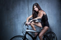Sexy girl in a black vest and shorts sitting on the bike on the background of gray textured wall Stock Photos