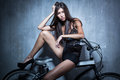 Sexy girl in a black vest and shorts sitting on the bike on the background of gray textured wall Royalty Free Stock Photography