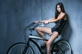 Sexy girl in a black vest and shorts sitting on the bike on the background of gray textured wall Royalty Free Stock Photos