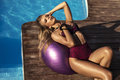girl with blond hair in bikini relaxing beside a swimming pool Royalty Free Stock Photo
