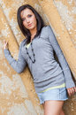 Sexy girl with brown hair fashion model woman female brunette dark wearing casual gray sweater and short denim mini skirt showing Stock Images