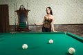Sexy girl in corset plays billiards russian pyramid Stock Photography