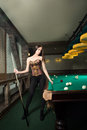 Sexy girl in corset plays billiards russian pyramid Royalty Free Stock Photos
